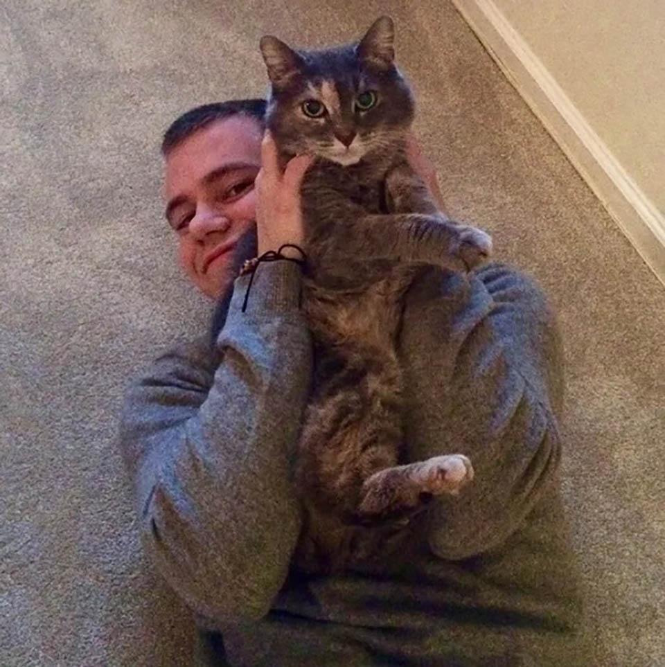 Hombre sostiene a su gata