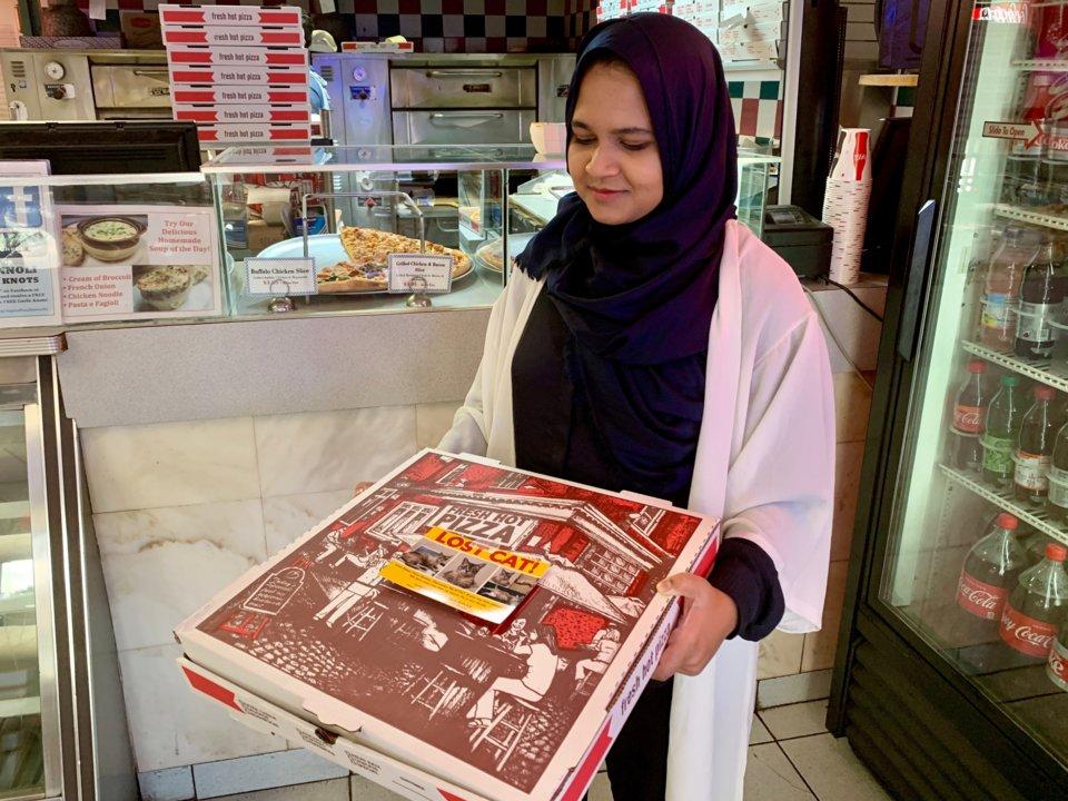 Mujer sostiene una caja de pizza con un folleto de un gato perdido