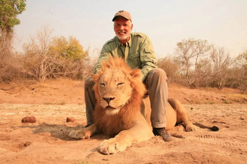 Hombre posa sobre león