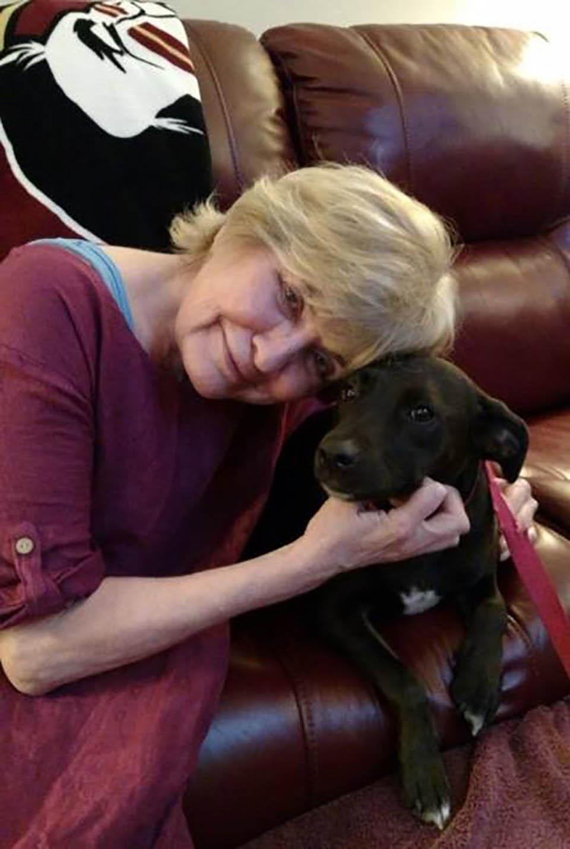 Adulta mayor acaricia a perrito negro
