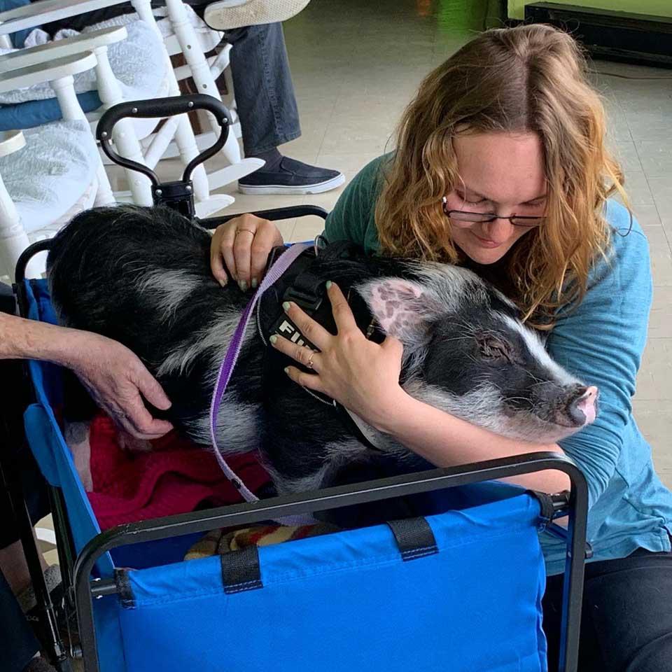 Mujer abraza a cerdita terapeuta