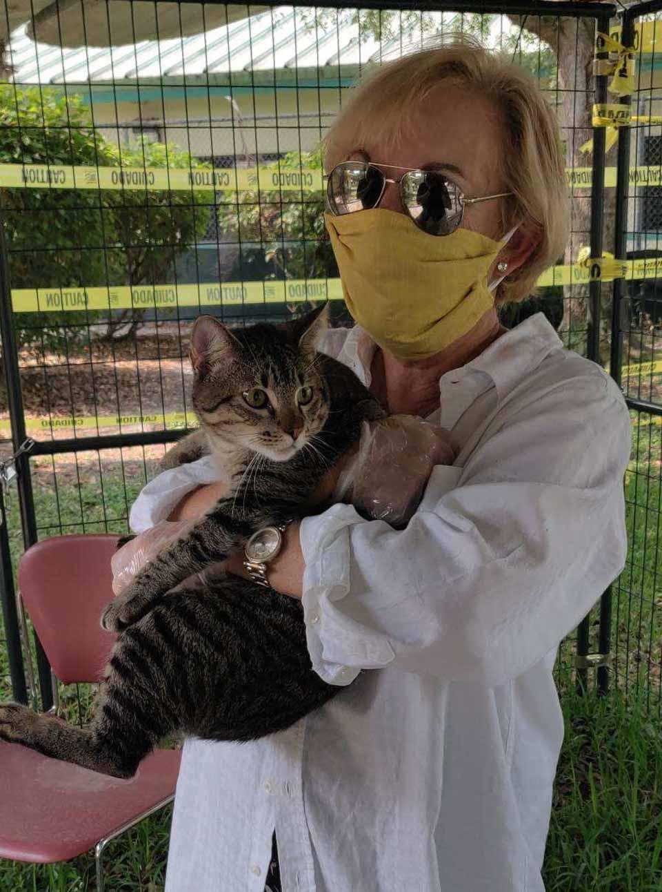 Mujer con tapabocas sostiene a gatito