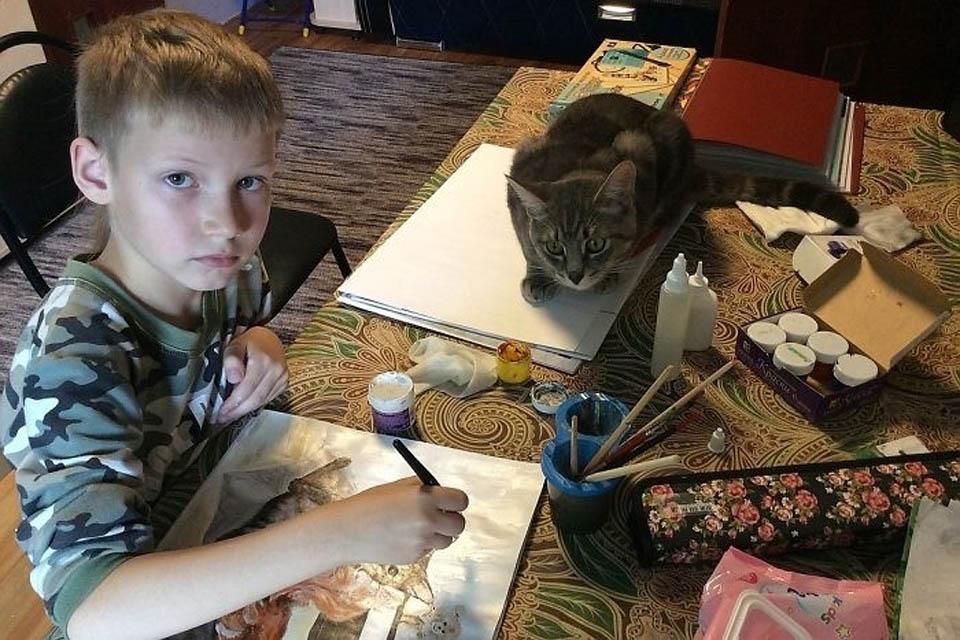 Niño y gato en una mesa