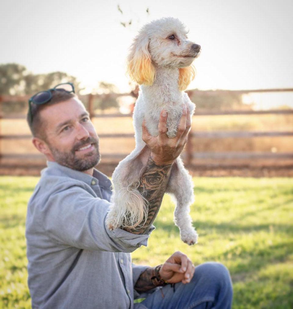 Hombre alza a su perrita caniche