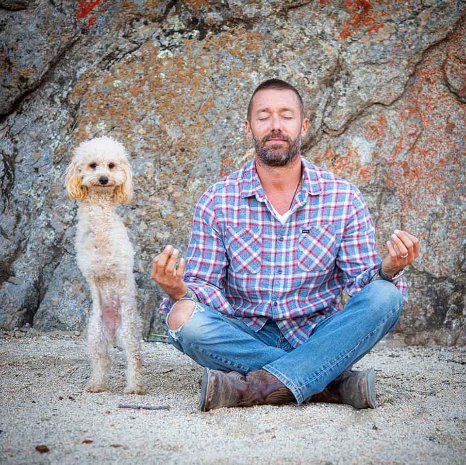 Hombre medita en compañía de su perrita