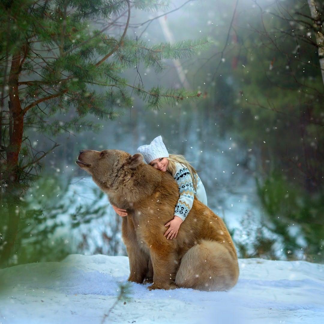 Mujer abraza a oso en la nieve