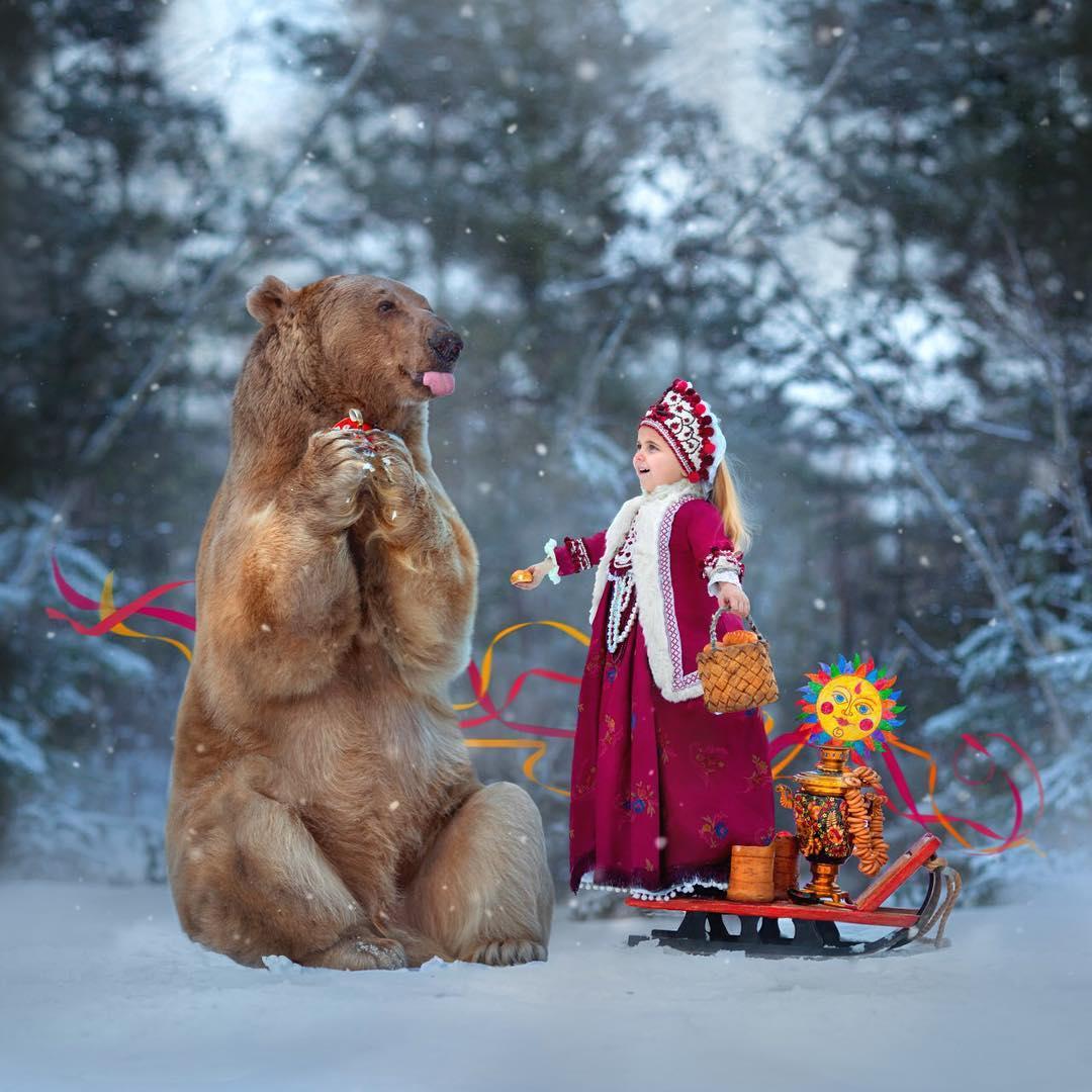 Niña posa en la nieve junto a oso